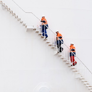 three men in orange and wearing hardhats climbing storage tank stairs